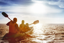 Family Of Father Mother And Son Kayaking At Sea Sunset