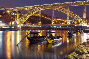Obraz na Szkle Miasta Traditional rabelo boats with barrels of Port wine on the Douro river, Ribeira and Dom Luis I or Luiz I iron bridge on the background, Porto, Portugal.