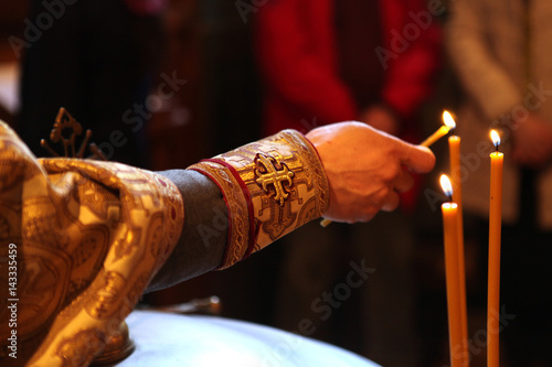 the Orthodox priest lights the candles during the baptismal ceremony Canvas-taulu