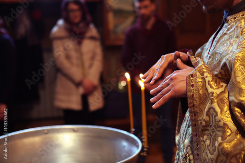 the Orthodox priest during the baptismal ceremony Canvas-taulu