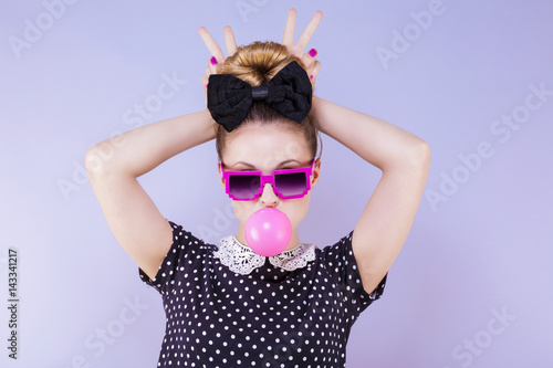 Portrait humoristique d'une jeune femme faisant une bulle de chewing gum les doi Canvas Print