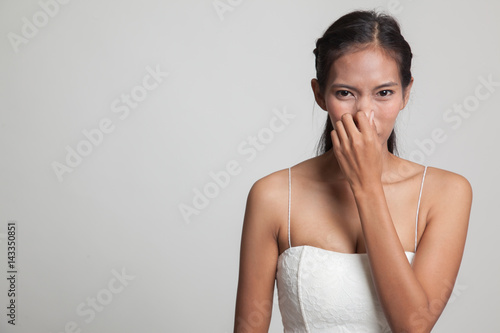 Fotografie, Obraz  Young Asian woman  holding her nose because of a bad smell.