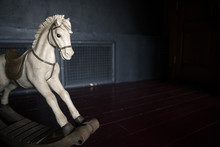 Old Vintage Rocking Horse On The Background Of Dark Wall.