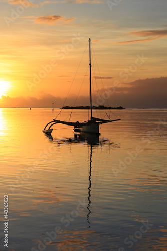 Foto auf AluDibond Pier Silhouette of a sail boat at sunset at sea. Amazing colorful sunset on the beach of Moorea, French Polynesia.