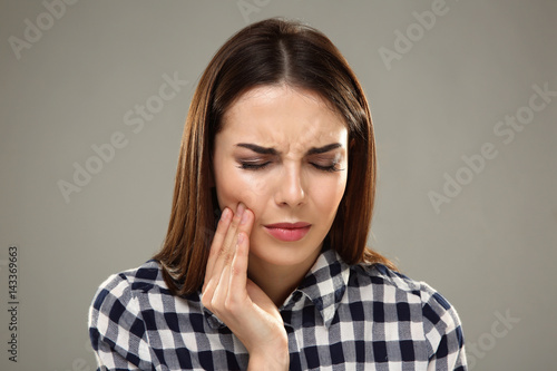 Carta da parati  Beautiful young woman suffering from toothache on grey background