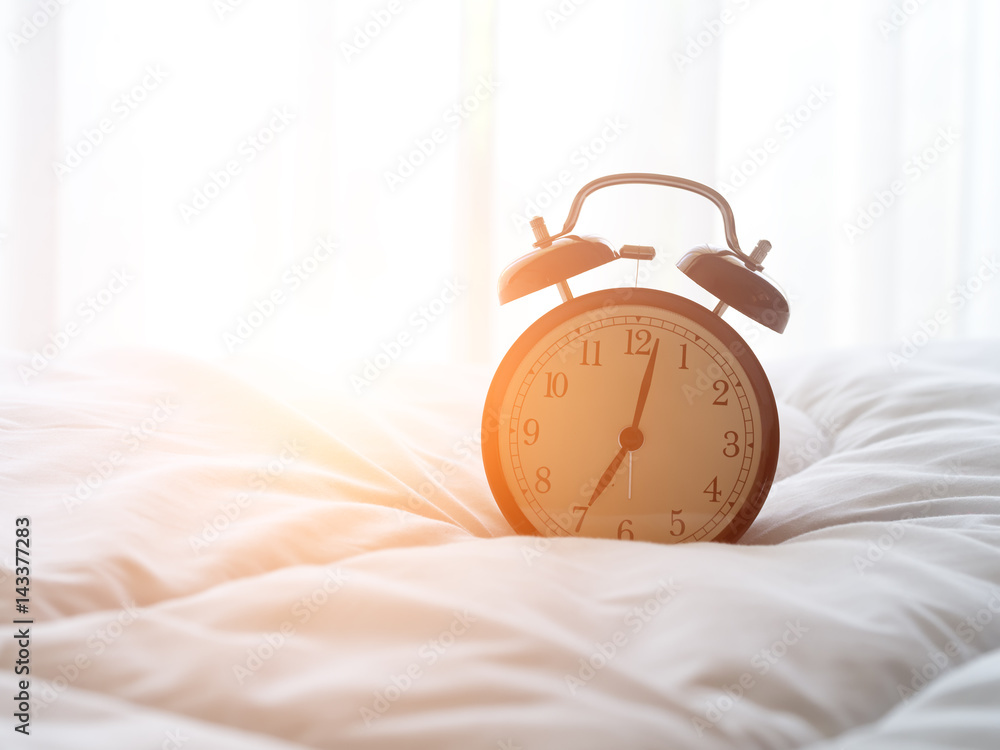 Fototapety, obrazy: Alarm clock on bed in morning with sun light..