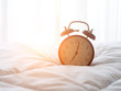 canvas print picture - Alarm clock on bed in morning with sun light..