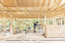 Sweden, Sodermanland, Carpenter Cutting Wooden Plank With Circular Saw On Construction Site