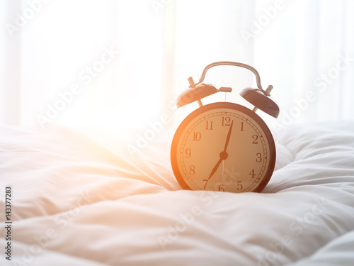 Alarm clock on bed in morning with sun light.. Fototapet