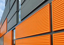 Architectural Background. Wall Of The Modern Orange And Black Corrugated Metal Panels.