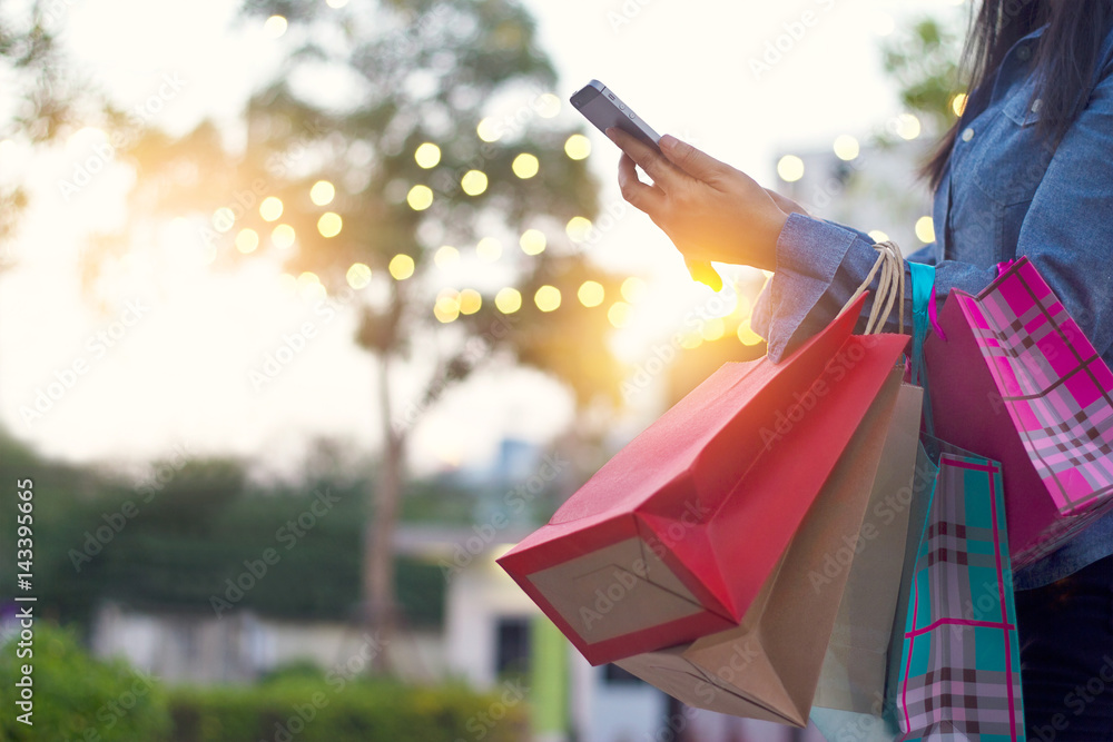Fototapety, obrazy: Woman using smartphone with shopping bags in hands