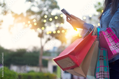 Vászonkép Woman using smartphone with shopping bags in hands