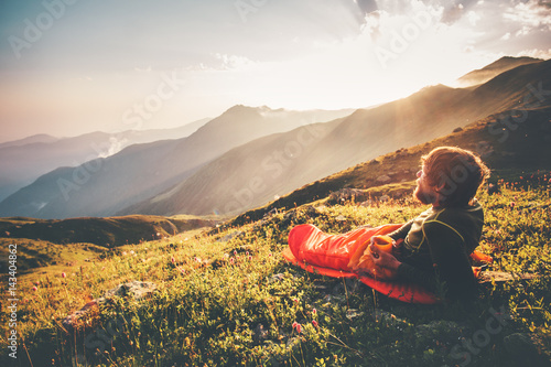 In de dag Kamperen Man relaxing in sleeping bag enjoying sunset mountains landscape Travel Lifestyle camping concept adventure summer vacations outdoor hiking mountaineering harmony with nature