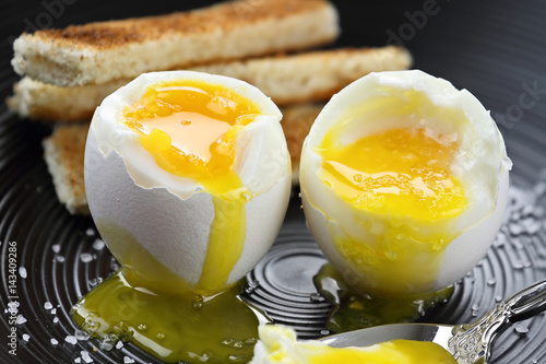 Valokuva  Two soft boiled eggs with toast soldiers in the background