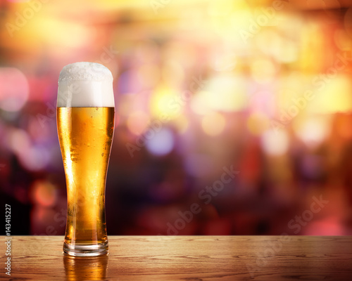 Papiers peints Biere, Cidre Golden Beer In Glass With Lights Of Bar In Background