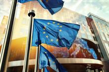 EU Flags Waving In Front Of European Parliament Building. Brussels, Belgium