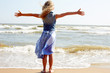 Happy child stands on the shore of the ocean with arms outstretched. Back view