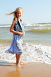 Happy child stands on the shore of the ocean