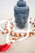 Buddha head in black lava and mala in semi-precious white stones for a yoga and meditation session