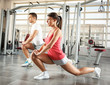 Young couple with sport body doing workout at the gym.They stretching her back and legs.