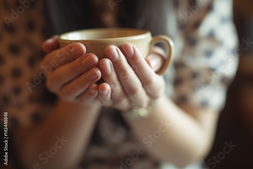 Mid section of woman holding a cup of coffee