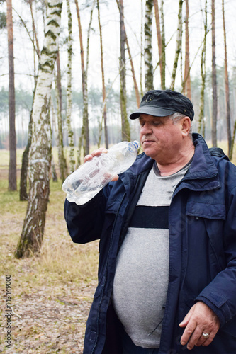 Valokuva  Mature caucasian man drinking water in the forest