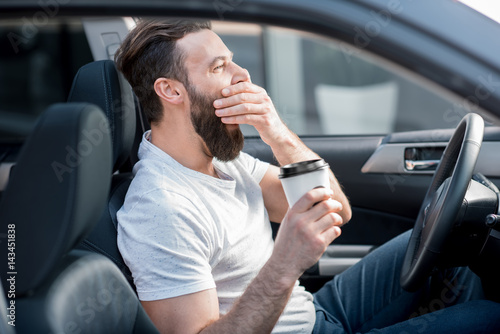 Fotografie, Obraz  Tired man yawning on the front seat of the car holding coffee to go