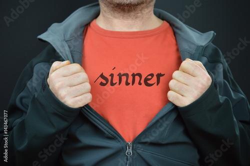 Fotografia Człowiek pokazujący jego t-shirt z napisem SINNER na nim napisany
