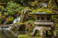Japanese Garden Waterfall And Statue In The Winter