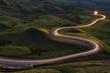 Leinwandbild Motiv Winding curvy rural road with light trail from headlights leading through British countryside.