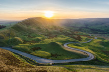 Sunset At Mam Tor In The Peak District With Long Winding Road Leading Through Valley.