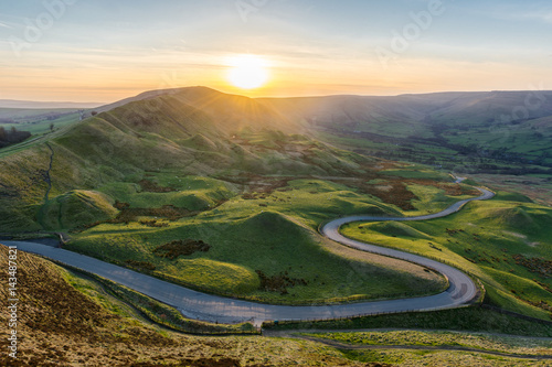 Photo  Sunset at Mam Tor in the Peak District with long winding road leading through valley