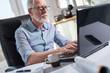 Portrait of senior businessman working on laptop, hard light