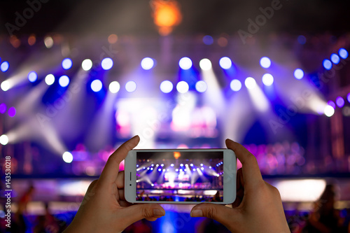 Fotografie, Obraz  Image of hands using camera phone to take pictures and videos at live concert