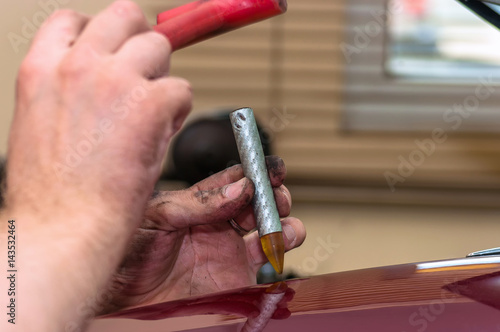 Fotografie, Obraz  Hands of car mechanic in auto paintless dent repair service.