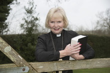Elderly Woman Vicar Leaning On A Garden Gate