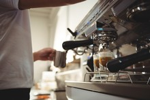 Barista Making Coffee Using Coffee Machine In Cafe