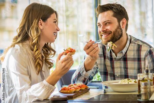 Plakat Para cieszy się lunchu obsiadanie przy kawiarnia stołem