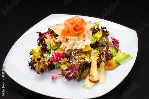 ciepła sałatka z ryb, warzywa na białym talerzu