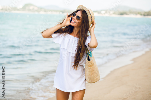 Cute stylish girl standing on a beach talking on a smartphone. Girl wears  straw hat 0f6e8b2aed4