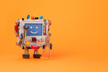 Fixing Computer Concept. Robotic Electrician With Hand Wrenches For Repair. Colorful Display Toy, Smile Message Blue Monitor. Service System Communication Concept. Orange Background, Copy Space.