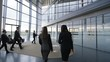 Businesswomen talking as they walk through modern glass office building