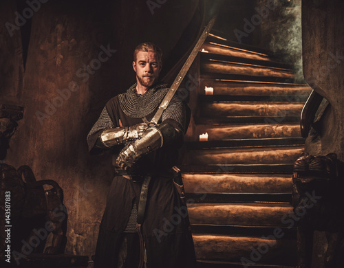 Foto  Medieval knight in ancient castle interior.