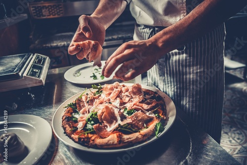 Fototapeta Food concept. Preparing traditional italian pizza. Chef in uniform decorate ready dish with green rucola herbs, ham, salami and prosciutto in interior of modern restaurant kitchen. Ready to eat. obraz