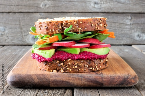 Staande foto Snack Superfood sandwich with beet hummus, avocado, vegetables and greens, on whole grain bread against a wooden background