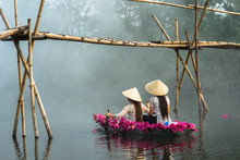 River Scene With A Boat Carrying Girls Wearing Traditional Dress Ao Dai, Conical Hat, And Flower. Smoke