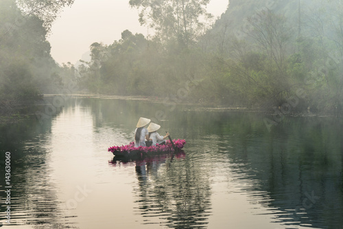 Poster Kaki River scene with smoke, a boat carrying girls wearing traditional dress Ao Dai, conical hat, and flower.