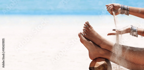 Poster Boho Stijl close up of woman pouring sand on her legs on beach