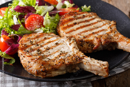 Grilled pork steak with bone and fresh salad close-up. horizontal