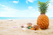 Ripe pineapples and sunglasses, seashell on the sandy tropical beach with clear blue sky. Leisure in summer and Summer vacation concept. vintage color tone.